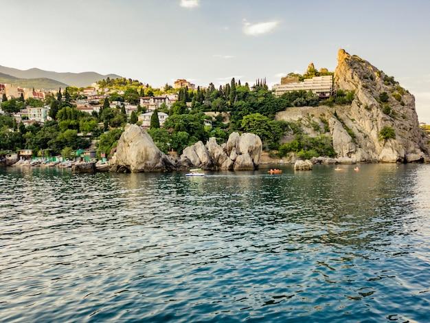 Aerial tourist in small catamaran near the rock sea coast in europe city bay
