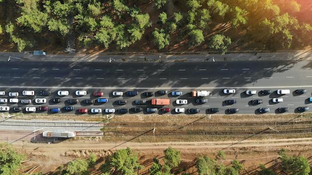 空中。森の間の高速道路でたくさんの車が渋滞している。ピーク時間。ドローンからの上面図。