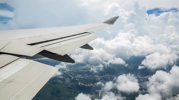 空中旅行。雲の中を飛んでいます。飛行機の翼の下の地面は雲の中に入ります。山のある香港の飛行機の窓からの眺め。航空機が飛ぶ。