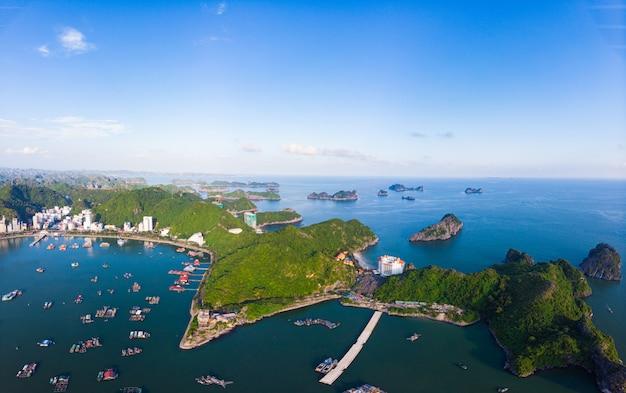 Уникальный вид с воздуха вьетнам cat ba bay с плавающие рыбацкие лодки на море, cloudscape тропическая погода вдохновляющие закат, эпический город и небоскреб, живописные зеленые горы.