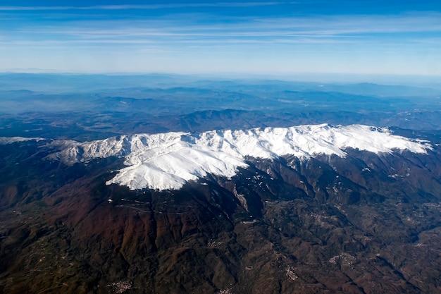 하얀 산봉우리, 안개 낀 수평선, 하늘이 있는 계곡의 공중 전망. 산을 지나가는 비행기의 창에서 경치를 볼 수 있습니다. 계곡의 눈 볏과 언덕. 산 위의 비행
