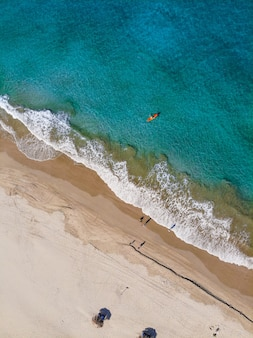 Aerial vertical shot of people on the beach shore at daytime