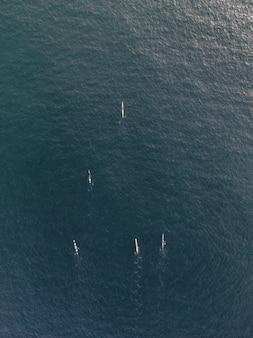 Aerial vertical shot of people in kayak boats paddling in a calm clear ocean water