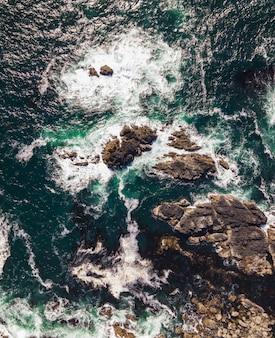 Aerial vertical shot of a sea with rocky stones