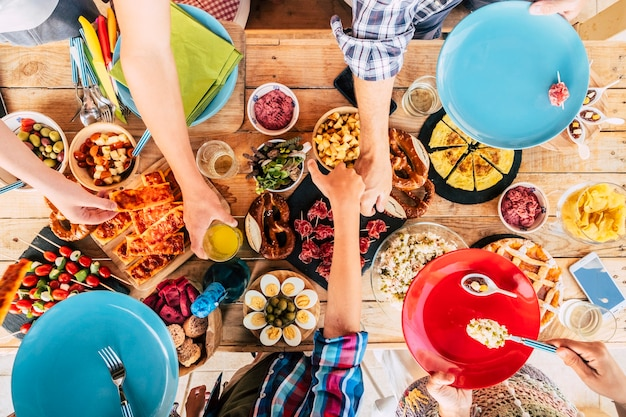 Aerial vertical view of table full of coloured traditional food and drinks and group of mixed ages generations people have fun celebrating together - concept of friendship and party