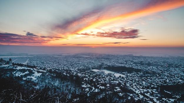 겨울에 눈으로 덮인 도시의 숨막히는 일몰 풍경을 공중보기