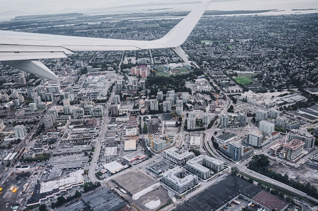 Aerial view of airplane wing on traffic in crowded city at vancouver, canada