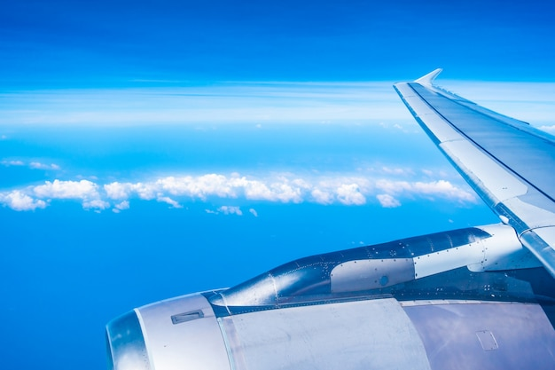 Aerial view of airplane wing with blue sky