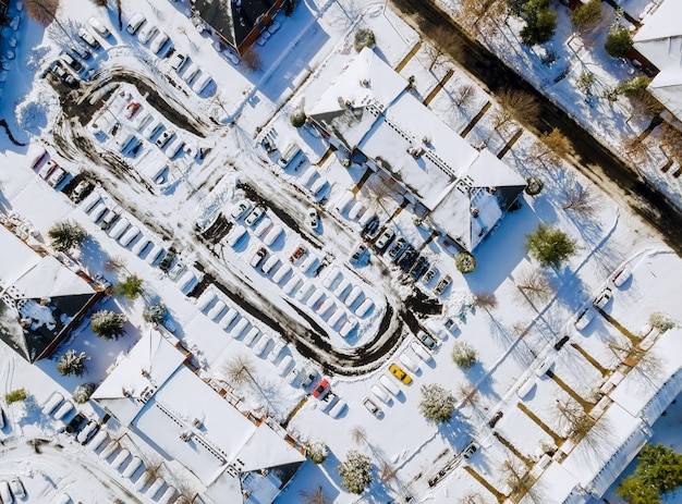 住宅の近所の屋根の家で覆われた雪で複雑な空撮アパート