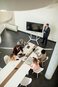 Вид с воздуха на группу деловых людей, работающих вместе и готовящих новый проект на встрече в офисе