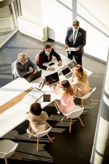 Вид с воздуха на многонациональную группу деловых людей, работающих вместе и готовящих новый проект на встрече в офисе
