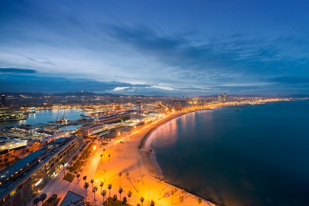Aerial view of barcelona beach in summer night along seaside in barcelona, spain.