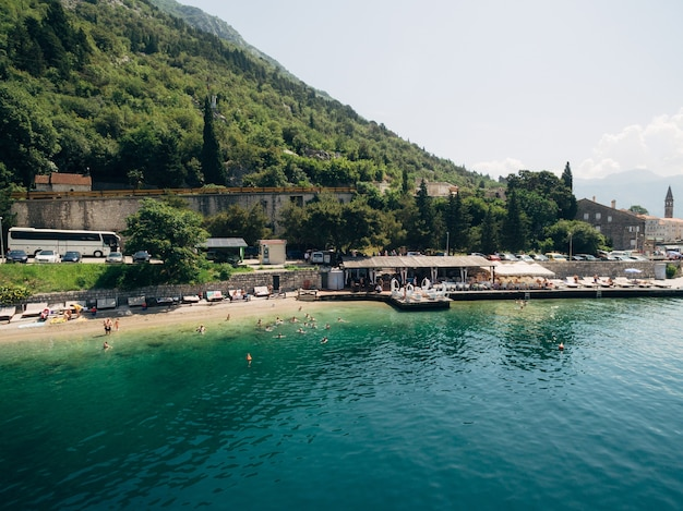 Aerial view of the beach of perast city with various buildings and green mountains in the background
