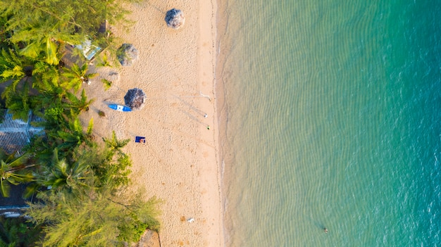 Aerial view of beach with shade emerald blue water and wave foam on tropical sea
