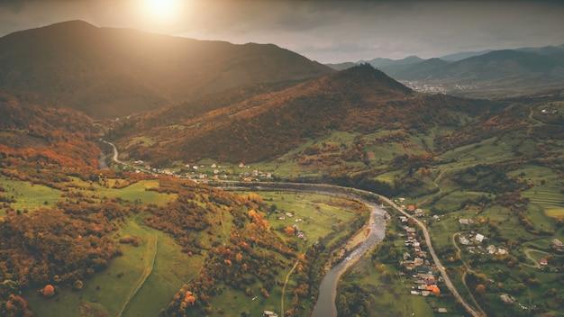 Вид с воздуха на красивую деревню каньона, расположенную вдоль реки, драматический осенний горный пейзаж с