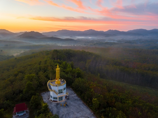 Aerial view beautiful fog and buddha statue in sunrise