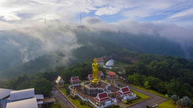 Aerial view beautiful fog and buddha statue in sunrise