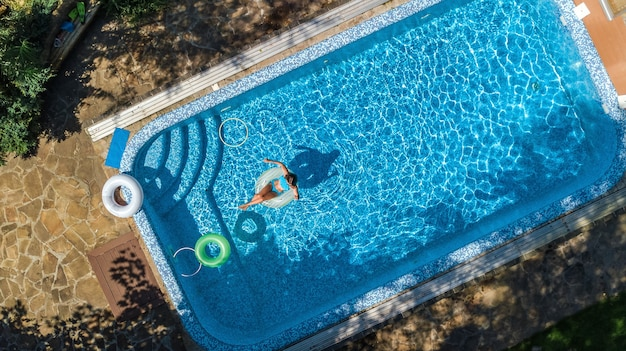 Aerial view of beautiful girl in swimming pool from above swim on inflatable ring donut and has fun in water on family vacation on tropical holiday resort