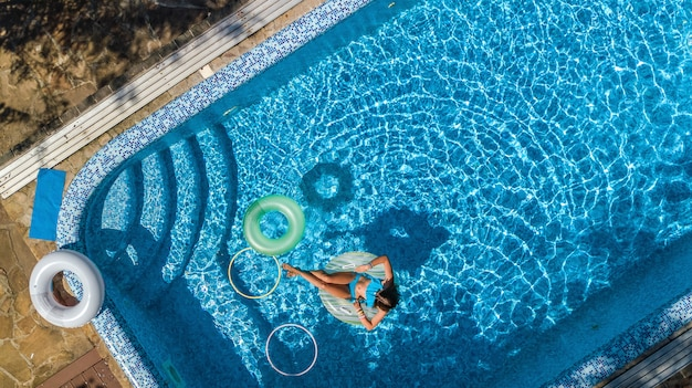 Aerial view of beautiful girl in swimming pool from above, swim on inflatable ring donut and has fun in water on family vacation on tropical holiday resort