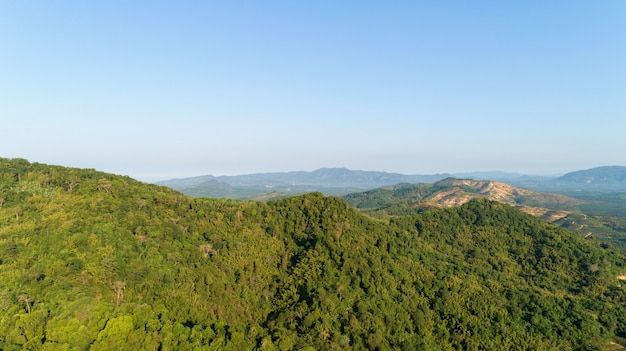 Aerial view of beautiful mountain landscape with mountain peaks covered with forest and blue sky in the morning.