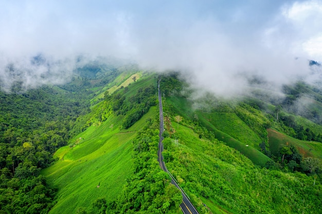 Aerial view of beautiful sky road over top of mountains with green jungle in nan province, thailand