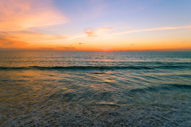 공중 보기 바다 표면 위에 아름 다운 보기 일몰 아름 다운 파도 모래 해안에 부서 지는 파도와 바다 해변 위에 놀라운 빛 일몰 또는 일출 하늘.