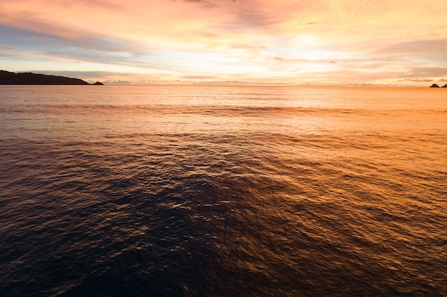 Aerial view beautiful view sunset or sunrise over sea surface beautiful wave amazing light golden sky sunset beautiful light of nature seascape.