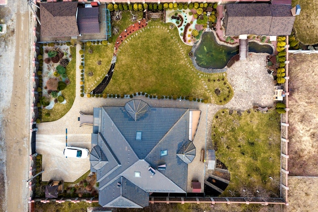 Aerial view of beautifully landscaped property complex. roofs of recreation house cottage, pond in ecological area on bright sunny day. modern architecture, landscaping concept.
