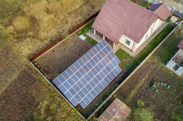 Aerial view of big blue solar panel installed on ground structure near private house.