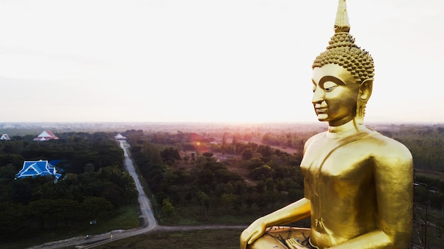 Aerial view of big golden buddha statue at sun rise, countryside of thailand