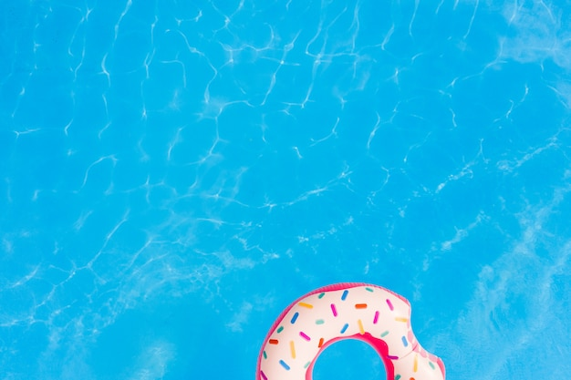 Aerial view of big pink donut in the swimming pool background