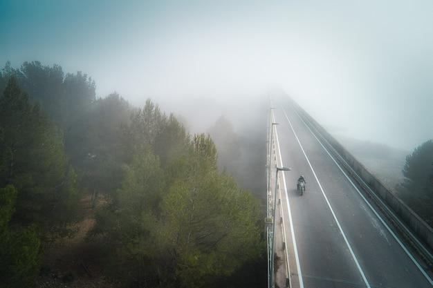 Vista aerea di un motociclista che attraversa un ponte coperto di nebbia