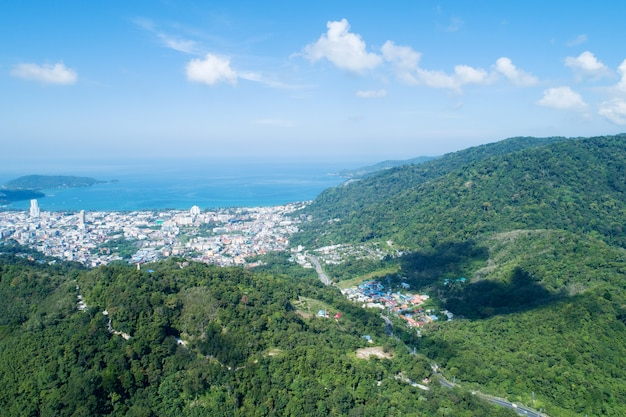 Aerial view blue ocean and blue sky with mountain in the foreground at patong bay of phuket thailand landscape of patong city phuket in sunny summer day time beautiful tropical sea high angle view.