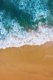 Aerial view of blue ocean wave on sand beach.