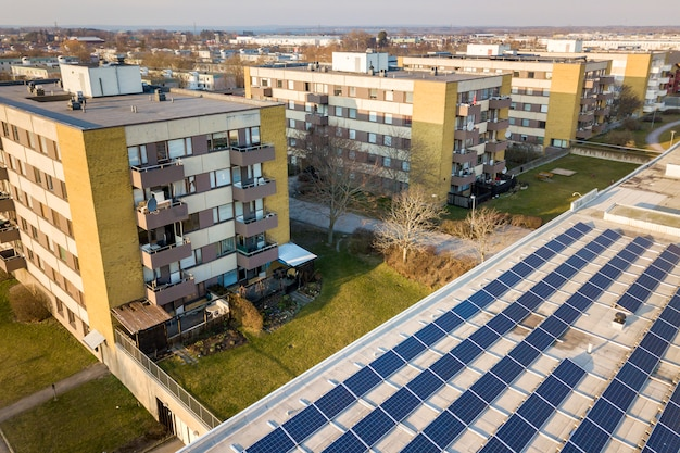 Aerial view of blue shiny solar photo voltaic panels system on commercial roof producing renewable clean energy on city landscape.