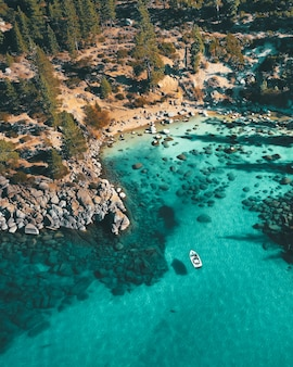 Aerial view of a boat on the water at the rocky beach
