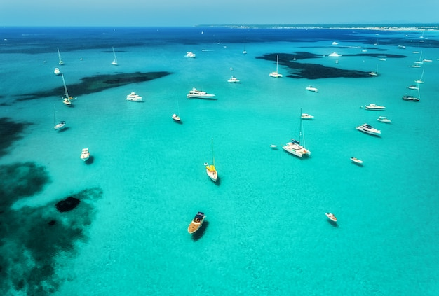 Aerial view of boats, luxury yachts and transparent sea at sunny day