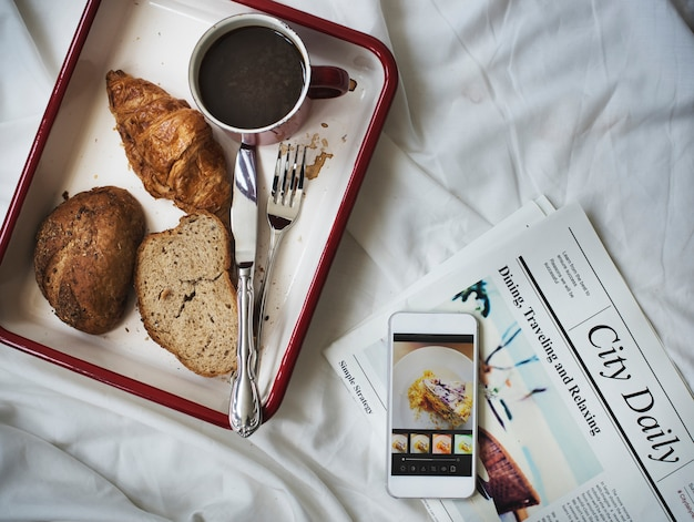 Aerial view of breakfast bread coffee in tray on bed