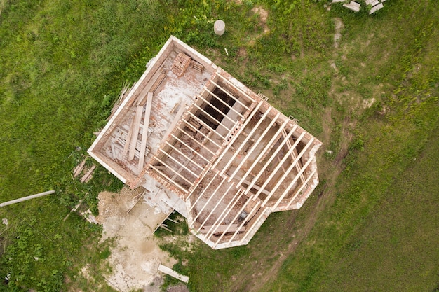 Aerial view of a brick house with wooden ceiling frame under construction.