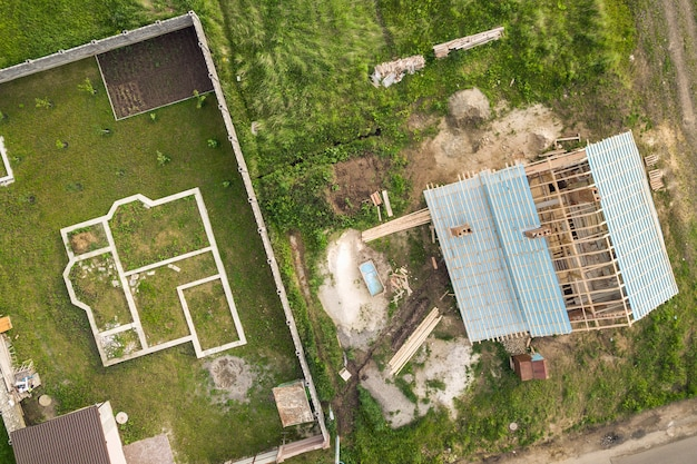 Aerial view of a brick house with wooden roof frame under construction and foundation for a new project.