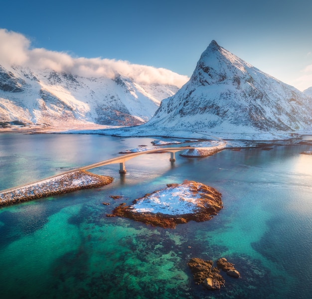 Aerial view of bridge over the sea and snowy mountains in lofoten islands, norway. fredvang bridges at sunset in winter.