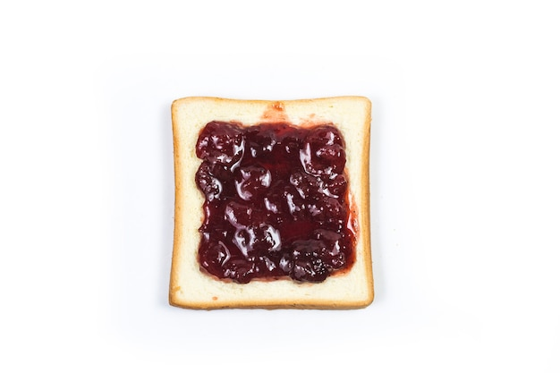 Aerial view of bright red strawberry preserves, spread over a slice of white bread