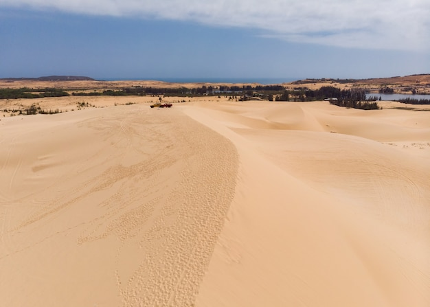 Aerial view of brown winding sand dunes with four-wheel car in muine, vietnam