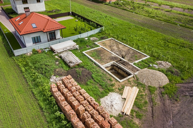 Aerial view of building site for future brick house, concrete foundation floor and stacks of yellow clay bricks for construction.