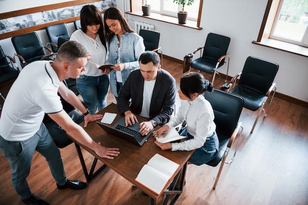 Vista aerea. uomini d'affari e manager che lavorano al loro nuovo progetto in classe