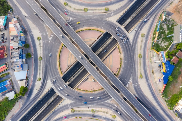 Aerial view above of busy highway road junctions at day. the intersecting freeway road overpass the eastern outer ring road of bangkok.