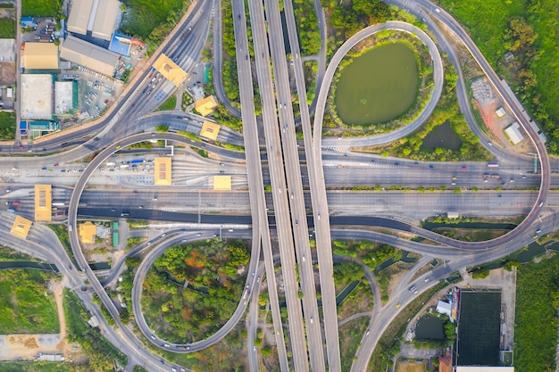 Aerial view above of busy highway road junctions at day. the intersecting freeway road overpass.