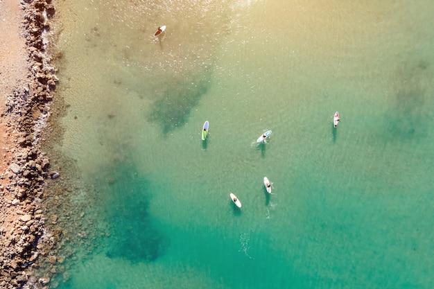 地中海のターコイズブルーの澄んだ海でスタンドアップパドルまたはsupを練習している人々のドローンによる空撮。