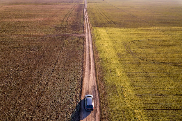 Aerial view of car driving by straight ground road through green fields on sunny blue sky copy space background. drone photography.