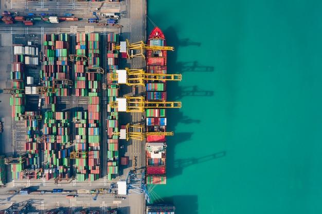 ビジネス物流輸送海上貨物、貨物船、世界中の輸入輸出のための工業団地の工場港の貨物コンテナーの空撮貨物船